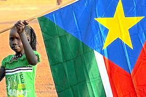 Picture: A young girl holds the South Sudan flag courtesy Timothy McKulka/USAID/Wikimedia Commons.