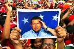 Picture: A picture of the immensely popular late Venezuelan president, Hugo Chavez, held aloft by his supporters, courtesy The Times.