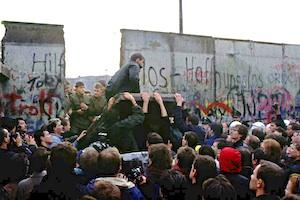 Picture: East and West Berliners tear down a portion of the Berlin Wall courtesy NPR.