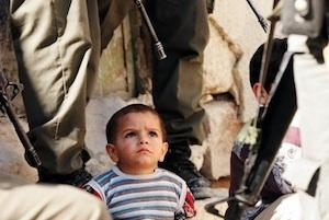 Picture credit: A Palestinian child surrounded by Israeli soldiers courtesy occupiedpalestine.wordpress.com.