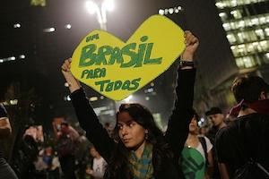 "Picture: A woman holds up a sign that reads ""One Brazil for all,"" in Sao Paulo, Brazil, where crowds gathered to celebrate the reversal of a fare hike on public transportation, courtesy Semilla Luz/Flickr."