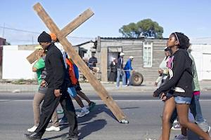 "Picture: Heavy cross to bear - community members from the township of Gugulethu hold a march to raise awareness of the ""hellish reality"" of township life (courtesy Abahlali baseMjondolo/flickr)."