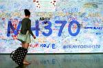 Picture: A Passenger walks past a banner filled with signatures and well-wishes for the missing passengers and crew of Malaysia Airlines MH370 at Kuala Lumpur International Airport (courtesy E&T Magazine)